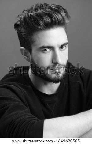 Close-up black and white portrait of a young handsome Caucasian male in studio. A man shows different human emotions.