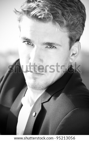 Close-up black and white portrait of beautiful young man turning toward viewer