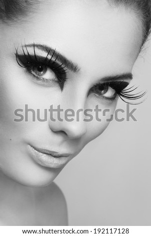Close-up black and white portrait of young beautiful woman with stylish make-up and huge false eyelashes
