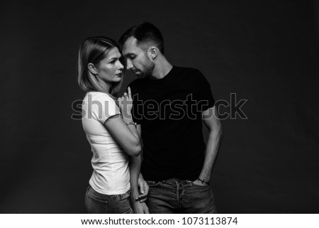 Close up black and white studio portrait of stylish young couple, pretty woman and handsome man, against plain studio background. #1073113874