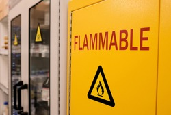 Close up black flammable sign with    red letter flammable on doors of   yellow flammable cabinet in laboratory room
