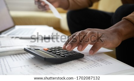 Close up black man hand using calculator and laptop for calculating finance. African american businessman taxing, accounting, statistics and credit analytic for mortgage payment.