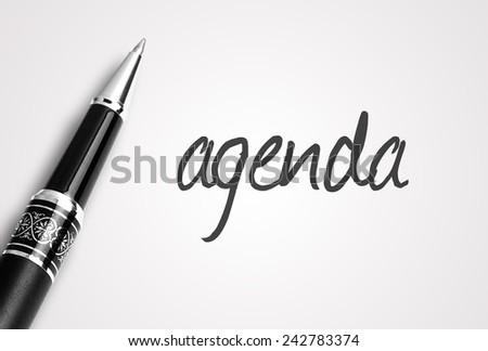 Close up black pen writes agenda on paper