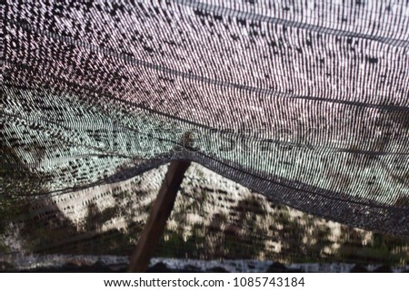 Close up black shading net pattern texture and background.Weaved plastic shade/ covers plants and materials to protect and avoid direct sunlight that could harm the object underneath. #1085743184