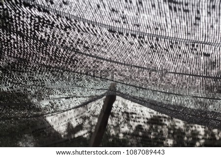 Close up black shading net pattern texture and background.Weaved plastic shade/ covers plants and materials to protect and avoid direct sunlight that could harm the object underneat. #1087089443