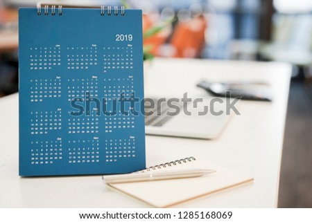 close up blue color calendar 2019  standing on white table at office room for make appointment or remind important date , workplace with object concept