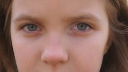 Close up blue eyes of unhappy little blonde girl blinking and looking into camera with a despairing sight. Sorrowful gaze of small depressed child. Facial expression of disappointing female kid