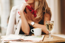 Close-up blur portrait of elegant woman wears red scarf and wristwatch with glass of wine on foreground. Blonde girl in stylish coat spending time in restaurant enjoying beverages and waiting friend.