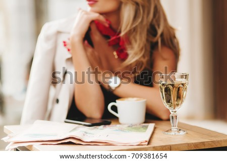 Close-up blur portrait of elegant woman wears red scarf and wristwatch with glass of wine on foreground. Blonde girl in stylish coat spending time in restaurant enjoying beverages and waiting friend. #709381654