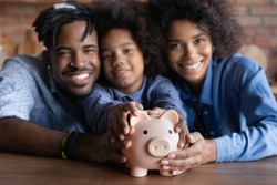Close up blurred portrait of smiling young African American family with daughter recommend saving money in piggybank. Happy ethnic parents with small child feel economical make financial investment.