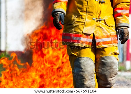 close up body of Firefighters In a fireproof suit  on a background of fire.selective focus