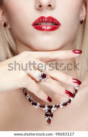 close-up body part portrait of beautiful woman with healthy skin, red manicure and jewellery