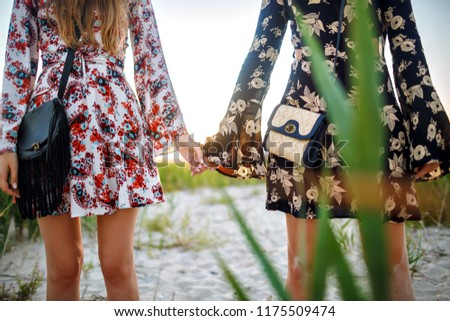 Close up boho style image of two woman holding hands, elegant vintage dresses and trendy bags, posing on the beach, fashion detailing. #1175509474