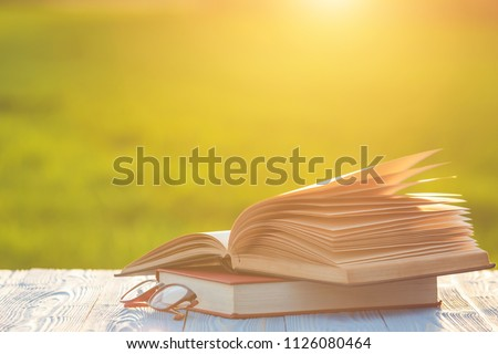 Close up book and eye glasses on wooden table with abstract blur and bokeh in sunrise or sunset time #1126080464