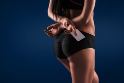 close up booty woman on blue background. clothing holding a business card , rear view