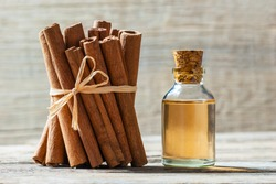 Close up bottle of cinnamon oil with cinnamon sticks and cinnamon powder on wooden background, healthy spice concept Cinnamomum verum