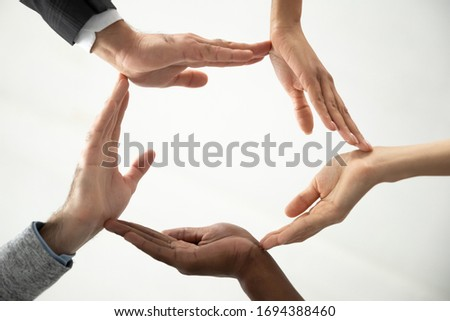 Close up bottom view concept of diverse business people join hands forming circle. Show unity and support, protection of business. Multiracial colleagues involved in team building activity.