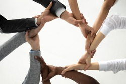 Close up bottom view concept of multiracial business people holding each others wrists, create hands circle. Support and unity team strength and power. Colleagues involved in team building activity.