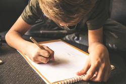 Close up bottom view of a young boy drawing a face on a white sheet. Kid hold a pencil and draw something, warm orange light at home. Children writing on a paper. Teen drawing sitting on a sofà
