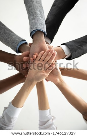 Close up bottom view vertical photo diverse business people stacking hands in pile at corporate meeting, colleagues employees engaged in team building activity at briefing, celebrating shared success