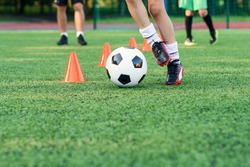 Close up boy in sportswear trains football on soccer field and learns to circle the ball between training orange cones.