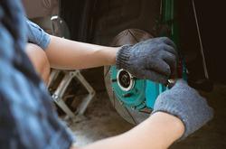 Close up brake caliper of car and a man remove pad brake in maintenance brake system process