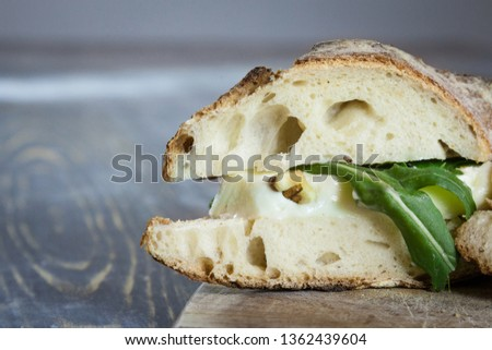 Close up Brie sanwdich in French baguette, made of Brie de Meaux Cheese with slices of rucola rocket salad and walnuts on a rustic wooden table. This sandwich, in France, is called sandwich au brie