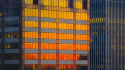 CLOSE UP: Burnt orange evening sky reflects off the windows of modern skyscrapers in the financial district of New York. Towering corporate building is illuminated by the stunning golden sunrise.