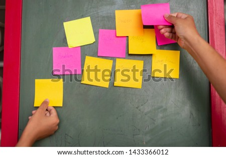 Close up business man hand holding note sticky for brainstorm and share idea strategy workshop business.Brainstorming concept. #1433366012