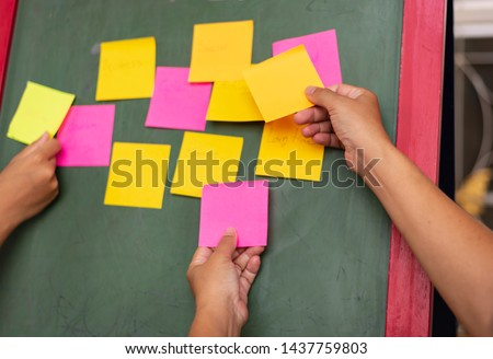 Close up business man hand holding note sticky for brainstorm and share idea strategy workshop business.Brainstorming concept. #1437759803