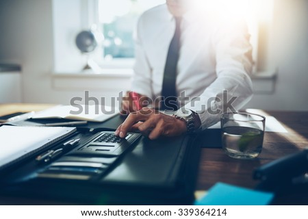 close up, business man or lawyer accountant working on accounts using a calculator and writing on documents