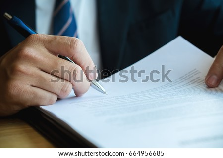 Close up business man reaching out sheet with contract agreement proposing to sign.Full and accurate details, individual who owns the business sign personally,director of the company, solicitor. #664956685