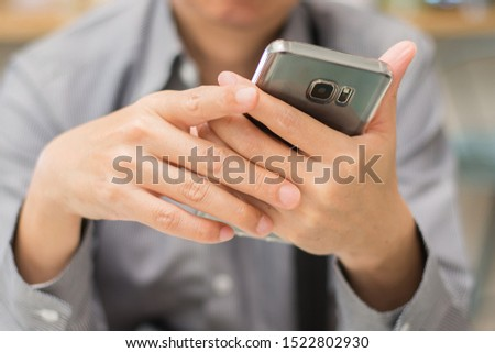 Close up business man wearing a shirt and holding smart phone or mobile phone on hands