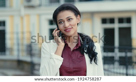 Close up business woman calling phone outdoors. Smiling mixed race woman having conversation on mobile phone outside. Cheerful female entrepreneur talking cellphone at urban street. ストックフォト ©