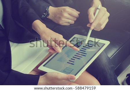 close up business woman hand finger point on screen display tablet for explain detail statistic graph with business man holding stylus pen for teaching. #588479159