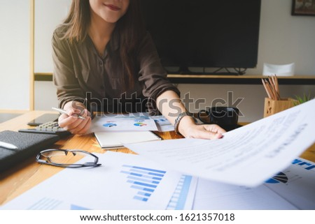 Close up Business woman hand holding pen and financial paperwork with financial network diagram. vintage concept.