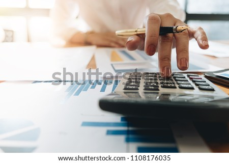 Close up Business woman using calculator and laptop for do math finance on wooden desk in office and business working background, tax, accounting, statistics and analytic research concept #1108176035