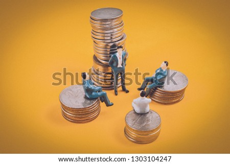 Close-up Businessman figure stands next to one coin stack and other businessman sit near on orange background with vignette effect. Concept of strategy meeting, board of shareholders, top-management d