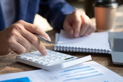 Close up businessman hand using calculator and working with  laptop calculate about finance accounting at coffeeshop outdor.finance accounting concept