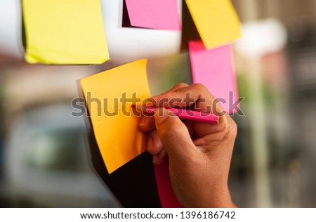 Close up businessman hand writing note sticky for brainstorm and share idea strategy workshop business.Brainstorming concept. #1396186742