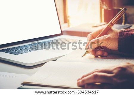 Photo of  Close up businessman hand writing working with modern computer