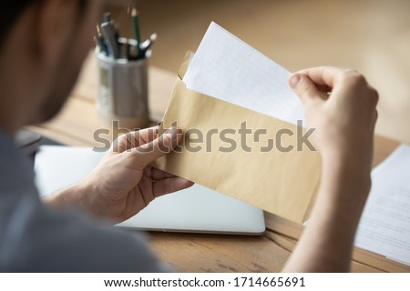 Close up businessman holding envelope with blank paper sheet, focused man looking at letter, received news, notification or invitation, working with correspondence, sitting at work desk Сток-фото ©
