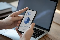 Close up businessman holding phone with graphs and diagrams on screen, analyzing startup project statistics, using smartphone, checking financial report presentation, sitting at work desk with laptop