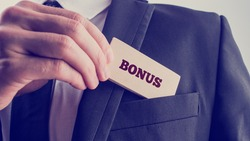 Close up Businessman in Black Suit Putting Small Wooden Piece with Bonus Text to Front Pocket. A Simple Company Bonus Concept.