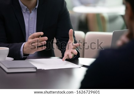 Close up businessman negotiating explaining agreement details to partner. Professional lawyer banker salesman real estate agent talking to client, discussing contract conditions, making offer propose.