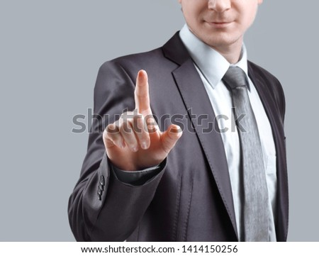 close up. businessman presses his finger on the virtual point. isolated on grey background
