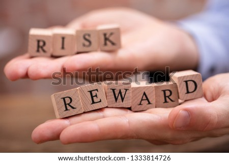 Close-up Businessman's Hand Holding Risk And Rewards Blocks Over Wooden Table #1333814726