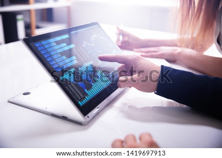 Close-up Businessman's Hand Pointing Bar Graph On Laptop Screen Over White Desk At Workplace
