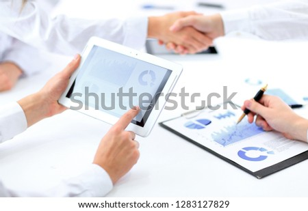 close up.businessman using a digital tablet to calculate the fin