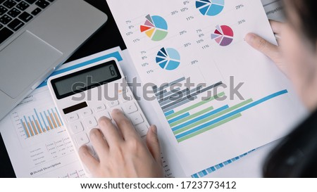 Close up Businessman using calculator and laptop for calaulating finance, tax, accounting, statistics and analytic research concept